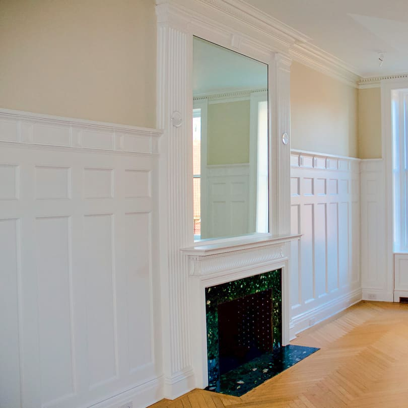 High raised-panel wainscoting surrounding a fireplace in a formal room