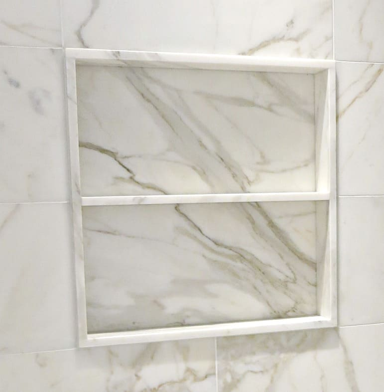 Square marble shower niche with one marble shelf and set slightly forward of the surrounding wall tile