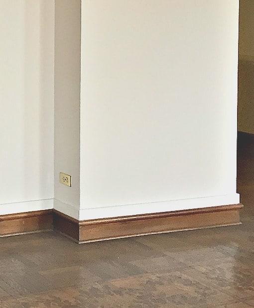 Stained mahogany quarter round shoe molding on stained mahogany base