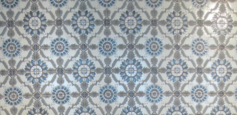 Backsplash tile with a blue and grey painted pattern