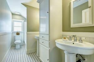 Remodeled bathroom with two pedestal sinks, tub toilet, black and white floor tile