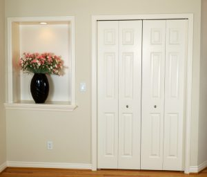 Pair of closet doors and adjacent wall niche with trim around them.