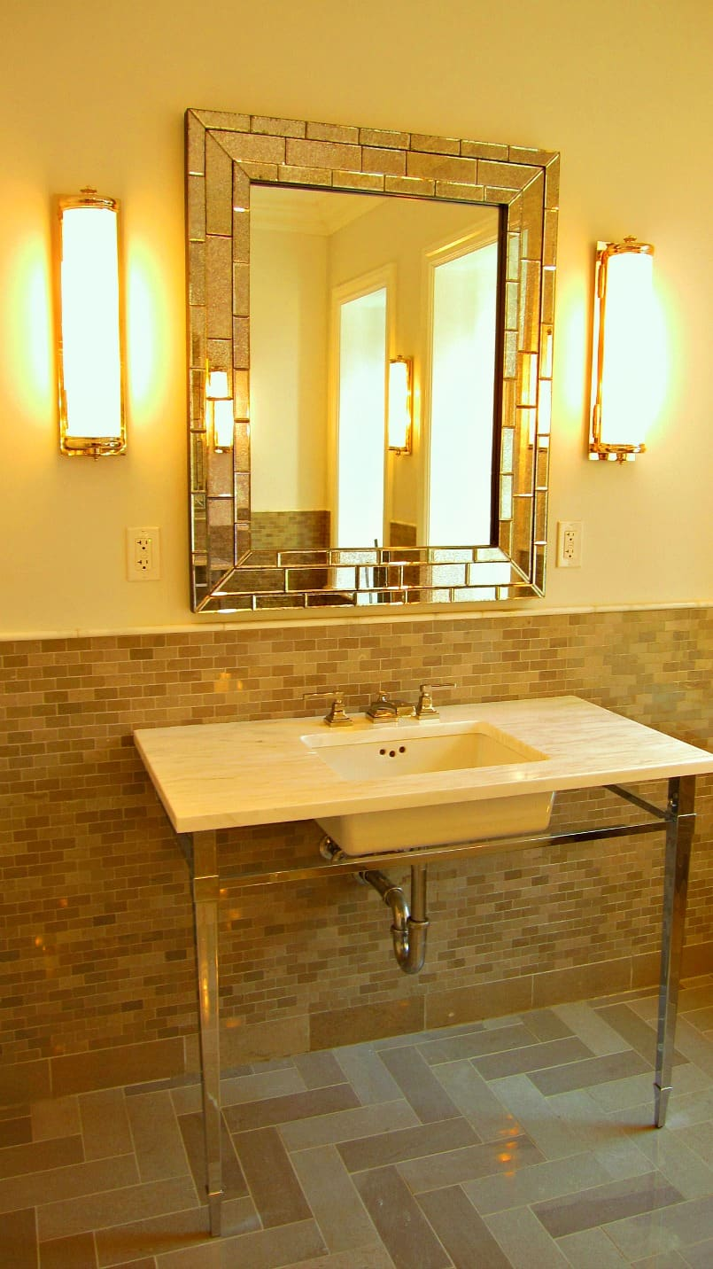 Pattern of floor and wall porcelain tile with variations of light brown colors in a bathroom with console lavatory, mirror and two sconces