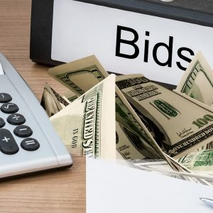 Bids sign on desktop with calculator and hundred dollar bids