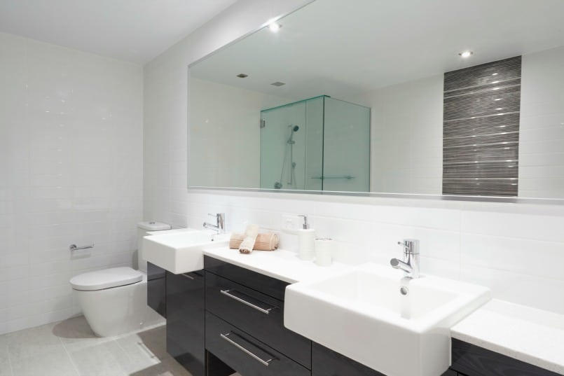 Double vanity with two white sinks mirror above and toilet beside
