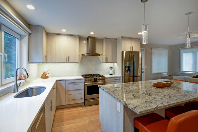 View of modern kitchen with island, counter lighting, tile backsplash and recessed lights.