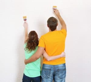 A couple with arms around one another while painting wall