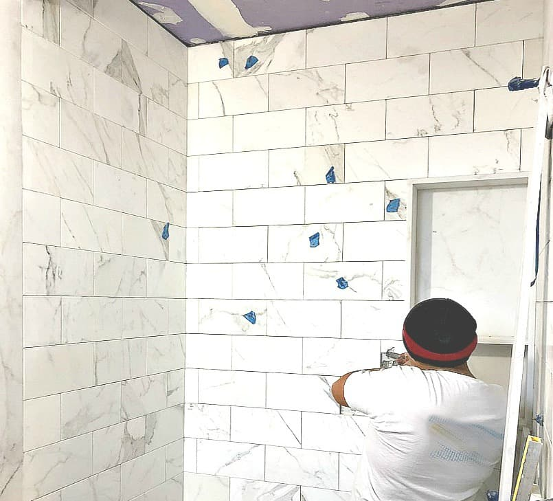 Worker Installing stone wall tile on bathroom shower wall
