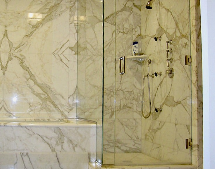 Glass shower enclosure and bathtub apron in white and grey marble
