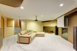 Basement media room with roll down screen and a couch lit by recessed lighting
