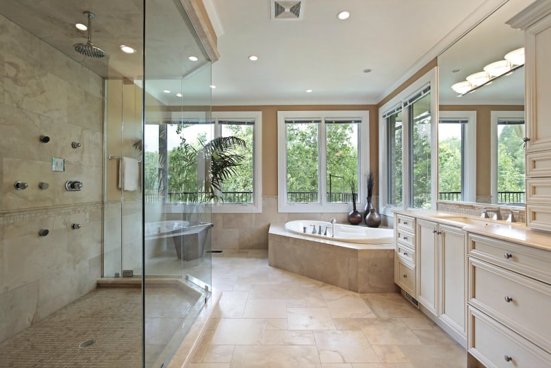 Large, complex renovated master bath with shower stall, frameless glass enclosure, beige floor tile, tub set into platform beneath windows and long vanity adjacent to the tub